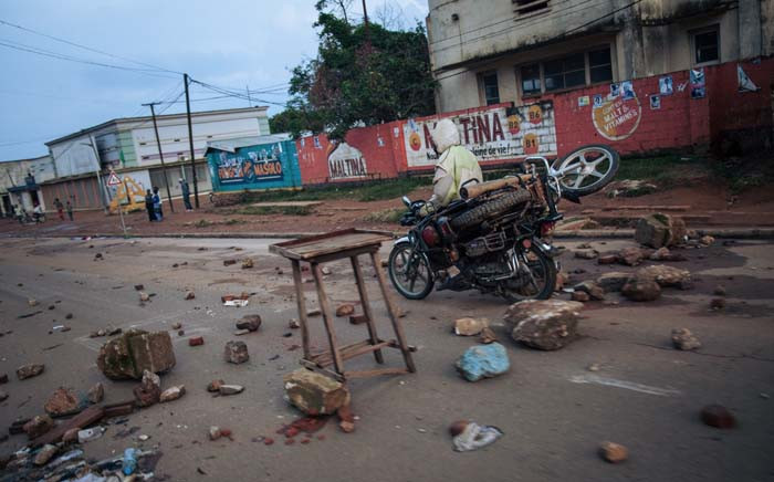 A man drives a motorcycle past rubbles at dusk in the main avenue of Beni following a demonstration against the postponement of elections in the territory of the Beni and the city of Butembo, on 27 December 2018. A DR Congo opposition bloc called for a nationwide stoppage and police clashed with demonstrators in two eastern cities after upcoming elections were placed on hold in their region. Picture: AFP