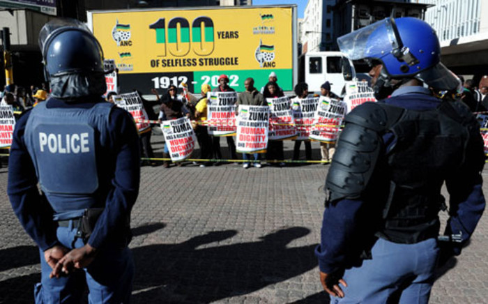 Police monitor protesters outside the South Gauteng High Court. Picture: Sapa.