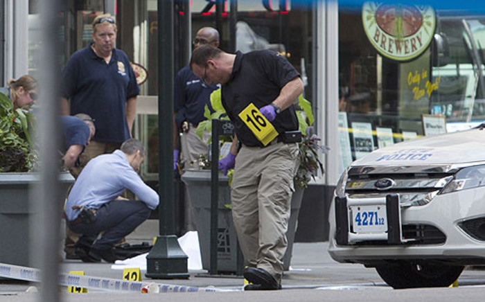 Law enforcement stands near the covered body of a suspected shooter on 5th Ave. near the Empire State Building 24 August 2012. Picture: AFP