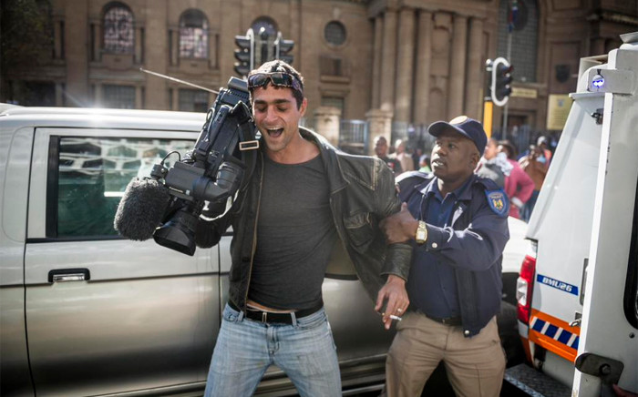 Journalist and Pierre le Roux pulls away from a Metro Police officer who was trying to grab his camera outside High Court in Johannesburg following a scuffle. Picture: Cornel van Heerden.
