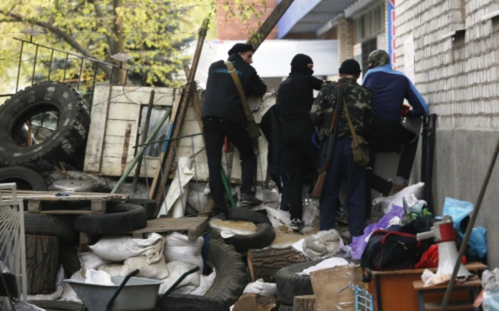 Pro-Russian protesters talk to each other at a barricade in front of the building of the city police department in Slavyansk on 19 April. Picture: AFP.