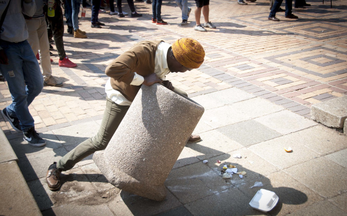 """A student tries to break a concrete dustbin for ammunition during skirmishes with private security at Senate House at Wits University. Picture: Nina Leslie/iWitness"