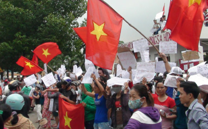 Protesters wave flags and hold placards on a street outside a factory building in Binh Duong on 14 May, 2014, as anti-China protesters set more than a dozen factories on fire in Vietnam. Picture: AFP.