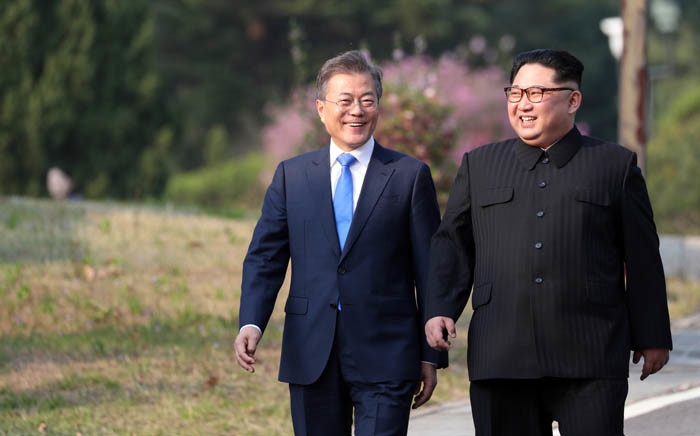 FILE: North Korea's leader Kim Jong Un (right) and South Korea's President Moon Jae-in (left) walk together after a tree-planting ceremony at the truce village of Panmunjom on 27 April 2018. Picture: AFP.