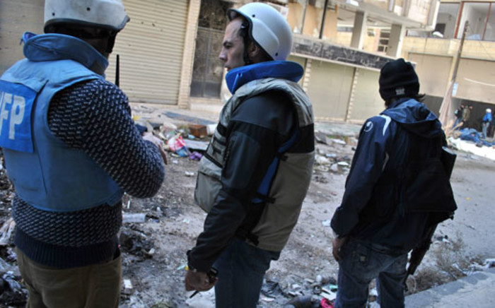 FILE: United Nations World Food Programme workers stand near a rebel fighter in a street on February 8, 2014 on the second day of a humanitarian mission in a besieged district of the central city of Homs. Picture: AFP.