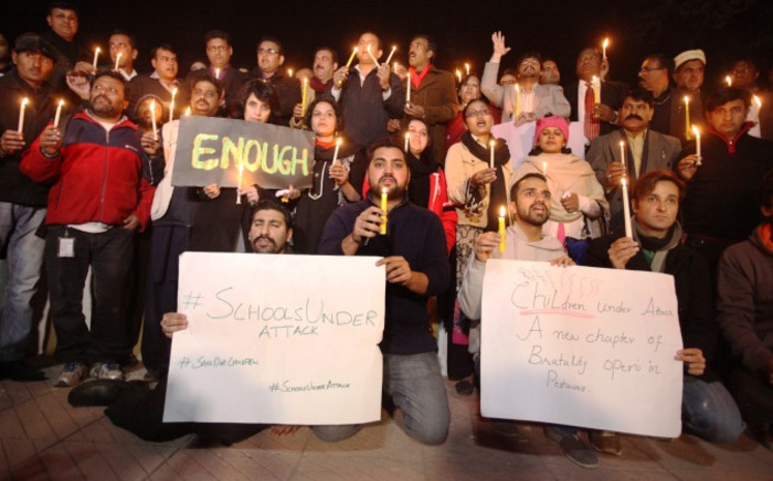 Members of Pakistani civil society and journalists light candles for the victims of an attack by Taliban gunmen on a school in Peshawar, in Islamabad on 16 December, 2014. Picture: AFP.