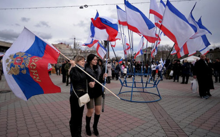 FILE: Two women hold a Russian flag next to a set of Crimean flags at Lenin Square in Simferopol on 16 March 2014. Crimeans voted on March 16 in a unique referendum on breaking away from Ukraine to join Russia. Picture: AFP.