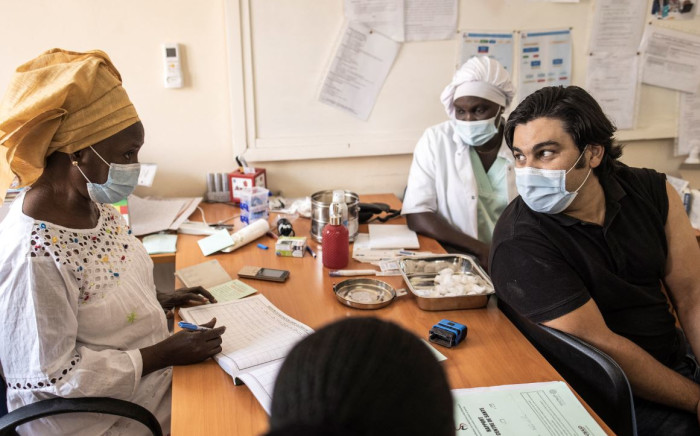 A man talks with a nurse after receiving a dose of the Oxford/AstraZeneca COVID-19 vaccine at Ngor Clinic in Dakar, Senegal, on 2 April 2021. Picture: AFP