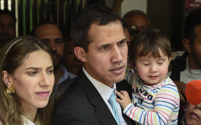 "Opposition leader and self-proclaimed ""acting president"" Juan Guaido (C) addresses the press as he holds his daughter Miranda, next to his wife Fabiana Rosales (L), outside his home in Santa Fe, Caracas on 31 January 2019. Picture: AFP"