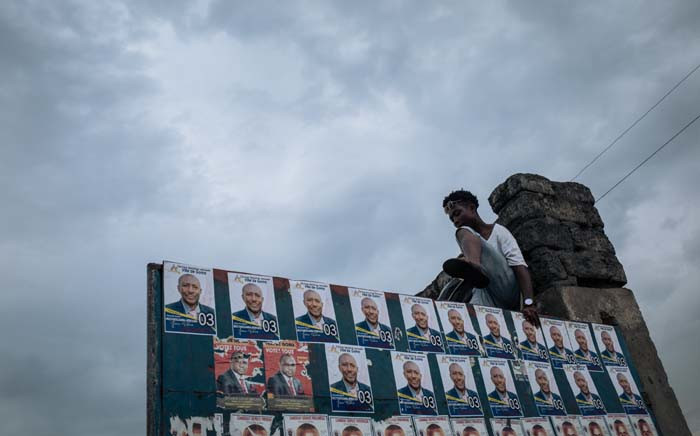 FILE: A citizen of Goma climbs up the wall at the entrance of Stadium 'des Volcans' during the election rally of the presidential candidate Emmanuel Ramazany Shadary in Goma, North-Kivu, on 16 December 16, 2018. Picture: AFP