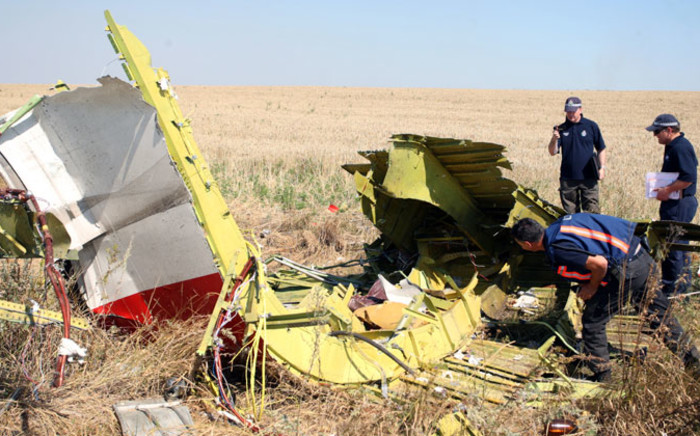 Australian and Dutch investigators examine a piece of debris of Malaysia Airlines Flight MH17, near the village of Hrabove, 100 km from Donetsk, Ukraine, on 1 August 2014. Picture: EPA.