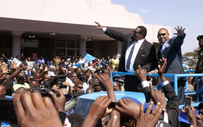 Malawi's newly elected President, Professor Peter Mutharika (2nd R), a young brother of the former late President Bingu wa Mutharika, and his Deputy Saulos Chilima (R) greet supporters after taking an oath of office at the High Court on 31 May 2014, in Blantyre, Malawi. Picture: AFP.