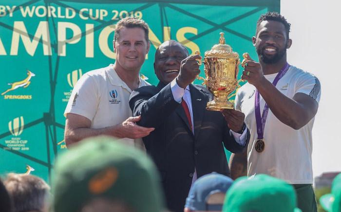 Springbok coach Rassie Erasmus (left) and captain Siya Kolisi (right) present the Webb Ellis Cup to President Cyril Ramaphosa at the Union Buildings in Pretoria on 7 November 2019. Picture: Abigail Javier/EWN