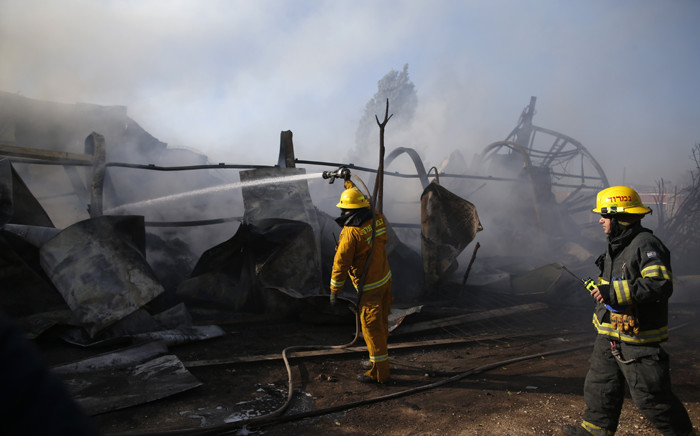 Israeli firefighters extinguish fire in Beit Meir, a religious cooperative village in the hills to the west of Jerusalem, on 25 November, 2016. Picture: AFP.