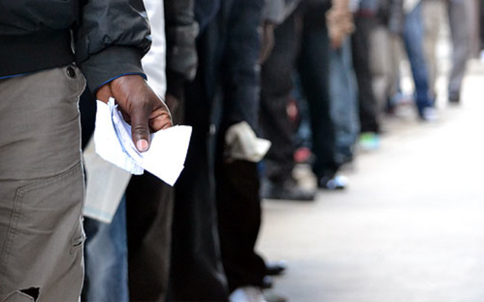 FILE: Asylum seekers stand in line with their documents outside a refugee centre. Picture: EWN
