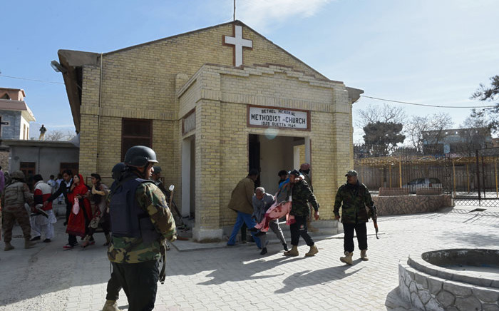 Pakistani security personnel rescue an injured woman after suicide bombers attacked a Methodist church during a Sunday service in Quetta on 17 December, 2017. Picture: AFP