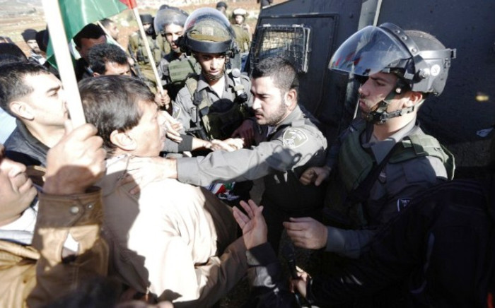 FILE: An Israeli border guard grabs Palestinian official Ziad Abu Ein (L), in charge of the issue of Israeli settlements for the Palestinian Authority, during a demonstration in the village of Turmus Aya near Ramallah, on 10 December, 2014. Picture: AFP.