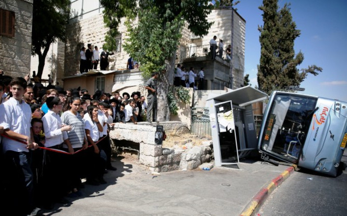 Israeli ultra-orthodox Jews watch as Israeli police work at the scene after a Palestinian man rammed an excavator into a bus (R), on 4 August, 2014 in Jerusalem, killing one person and lightly injuring five others. Picture: AFP.
