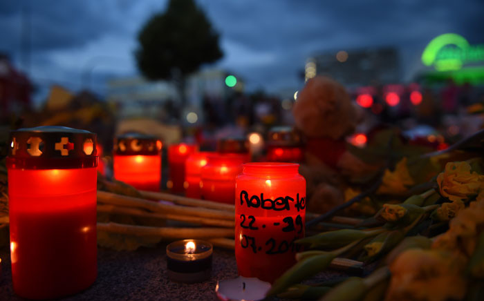 FILE: PoliFlowers and candles lie near the Olympia Einkaufszentrum shopping centre on 24 July 2016 in Munich, southern Germany, where an 18-year-old German-Iranian student run amok. Picture: Christof Stache/AFP.