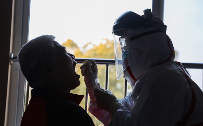 This photo taken on 4 February 2020 shows a medical staff member (R) taking samples from a person to be tested for the new coronavirus at a quarantine zone in Wuhan, the epicentre of the outbreak, in China's central Hubei province. Picture: AFP