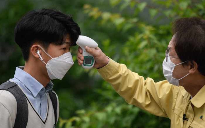 FILE: Students wearing facemasks amid concerns over the COVID-19 novel coronavirus undergo a temperature check from city education officials as they arrive at Kyungbock High School in Seoul on 20 May 2020.  Picture: AFP