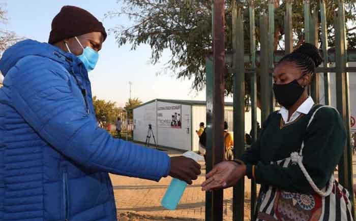 FILE: A teacher sanitises the hands of a pupil returning to Olivenhoutbosch Secondary School on 8 June 2020. Picture: Gauteng Provincial Government.