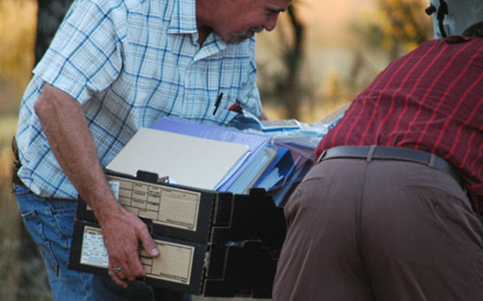FILE: Investigators carry files gathered from Nico Henning's properties. Picture: Barry Bateman/EWN.