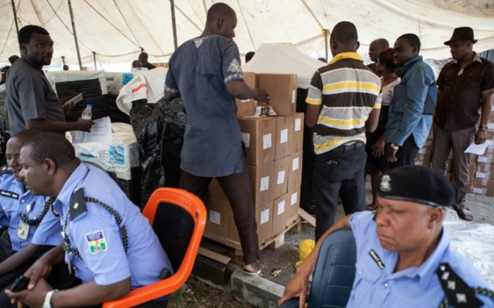 Police officers stand by as officials prepare voting materials at the Independent National Electoral Commission offices in the oil hub of Port Harcourt ahead of presidential elections on 28 March. Picture: AFP.