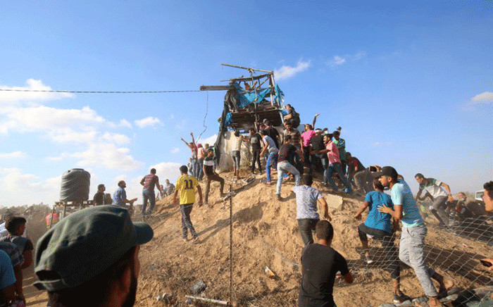 Palestinians gather and react at a Hamas outpost that was struck by Israeli bombardment near Khan Yunis in the southern Gaza Strip on 20 July, 2018. Picture: AFP.