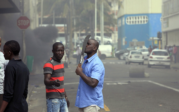 FILE: A foreign national holds a machete to protect himself after clashes broke out between a group of locals and police in Durban on 14 April, 2015 in ongoing violence against foreign nationals in Durban, South Africa. Picture: AFP.