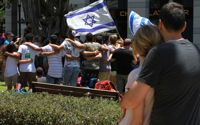 FILE: An Israeli couple looks towards people gathering at the restaurant targeted during a shooting attack the previous night at a shopping complex in Tel Aviv on 9 June 2016. Picture: AFP