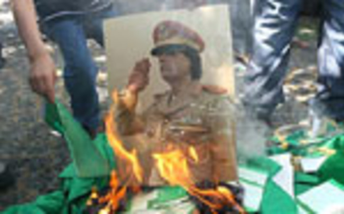 A portrait of Libyan leader Muammar Gaddafi is set on fire by demonstrators during a protest outside the Libyan embassy in Ankara on August 22, 2011. Picture: AFP