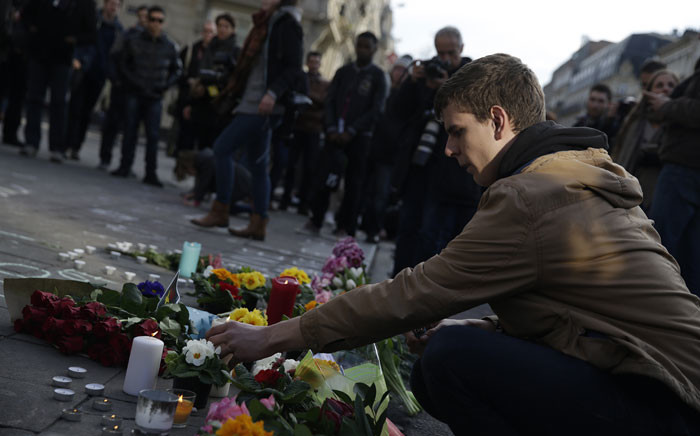 A man lights a candle at a makeshift memorial at Place de la Bourse (Beursplein) following attacks in Brussels on 22 March, 2016. Airlines cancelled hundreds of flights and European railways froze links with Brussels after a series of bomb blasts killed around 35 people in the city's airport and a metro train, sparking a broad security response. Picture: AFP.