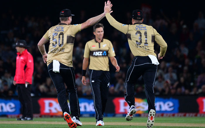 New Zealand's Jimmy Neesham (R) and Martin Guptill celebrate the dismissal of Australia's Matthew Wade during the first Twenty20 cricket match between New Zealand and Australia at Hagley Park Oval in Christchurch on 22 February 2021. Picture: Sanka Vidanagama/AFP