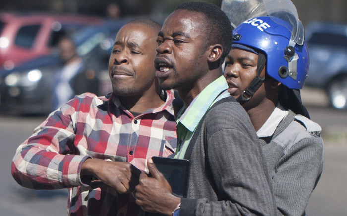 A Zimbabwean policeman arrests protesters during a demonstration on 6 July 2016, in Bulawayo. Picture: AFP.