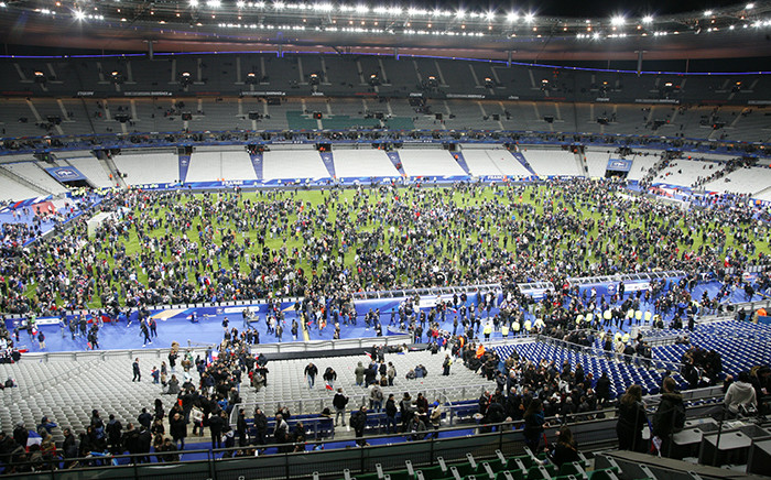 Spectators wait on the pitch of the Stade de France stadium in Seine-Saint-Denis, Paris' suburb on November 13, 2015 after a series of gun attacks occurred across Paris as well as explosions outside the national stadium where France was hosting Germany. Picture:AFP
