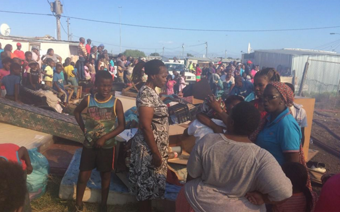 Residents at the fire scene in Gugulethu watching as the fire is being extinguished. Picture: Masa Kekana/EWN