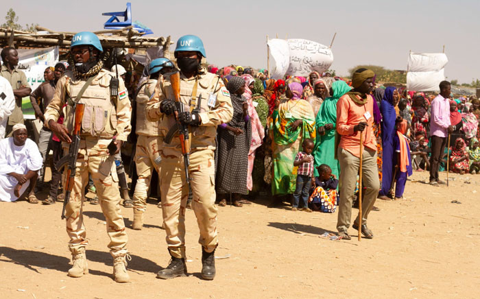 Members of the United Nations and African Union peacekeeping mission (UNAMID) look on as Sudanese internally displaced people stage a sit in to protest against the end of their mandate, in Kalma camp in Nyala, the capital of South Darfur, on 31 December 2020. Picture: AFP.