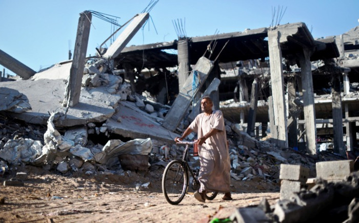 A Palestinian man pushes a bicycle past the rubble of destroyed buildings in Shejaiya on 27 August, 2014. Picture: AFP.