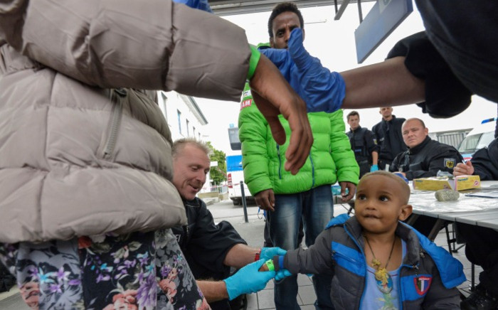 FILE: A young family from Eritrea is registered by the German Federal Police after departing a train from Verona at the southern German city of Rosenheim on 5 September 2015. Picture: AFP.