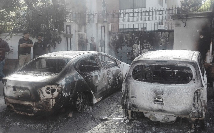 Pakistani security personnel stand next to burned out vehicles in front of the Chinese consulate after an attack in Karachi on November 23, 2018. At least two policemen were killed when unidentified gunmen stormed the Chinese consulate in the Pakistani port city of Karachi on November 23, officials said. Picture: AFP.