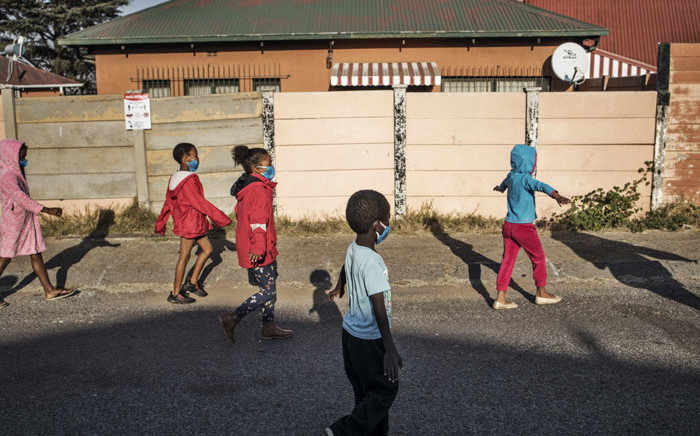 "FILE: Children wearing protective facemasks and extending their arms to enforce social distancing, walk with volunteers of the non-profit organisation and charity group ""Hunger has no Religion"" in Westbury, Johannesburg, on 23 May 2020. Picture: AFP"
