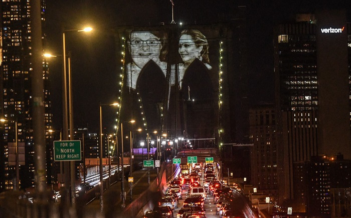 Images of New Yorkers lost to the COVID-19 pandemic are projected on to the Brooklyn Bridge on March 14, 2021 in New York City. New York City honours lives lost to COVID-19 on the anniversary of the one year anniversary of the COVID-19 lockdown. Stephanie Keith/Getty Images/AFP.