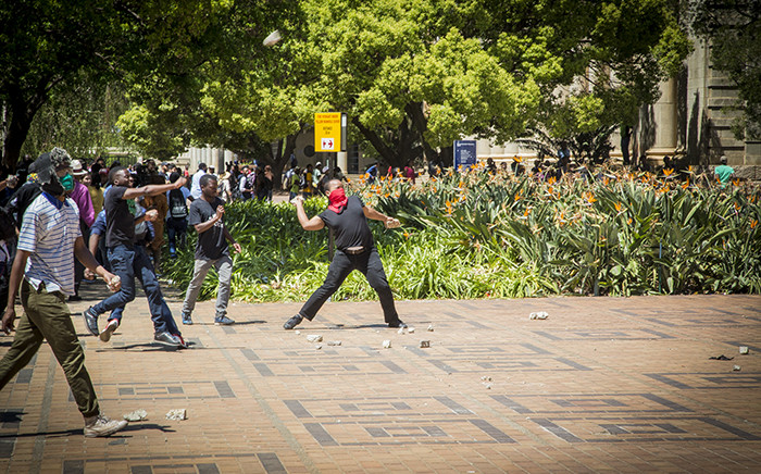 #FeesMustFall supporters hurl rocks at campus security standing at the Great Hall on Wits University's main campus on 11 October 2016. Picture: Reinart Toerien/EWN.