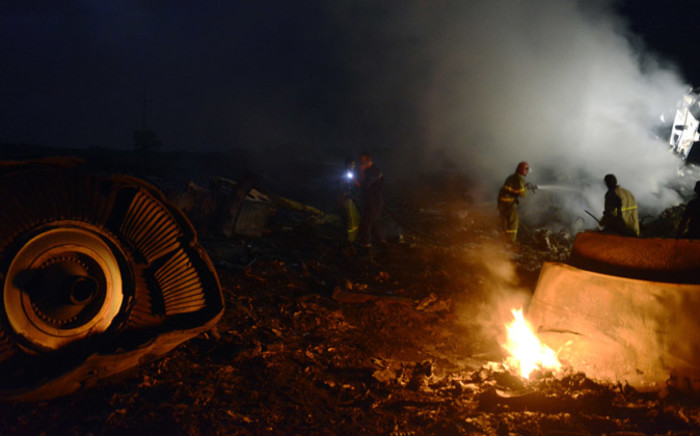 Firefighters extinguish a fire, on 17 July, 2014, amongst the wreckages of the Malaysian Airliner carrying 298 people from Amsterdam to Kuala Lumpur after it crashed, near the town of Shaktarsk, in rebel-held east Ukraine. Picture: AFP