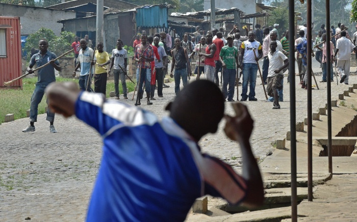 FILE. A protester opposed to the Burundian president's third term throws a rock at members of the Imbonerakure, the youth wing of the ruling party, armed with sticks in the Kinama neighborhood of Bujumbura on May 25, 2015. Picture: AFP.