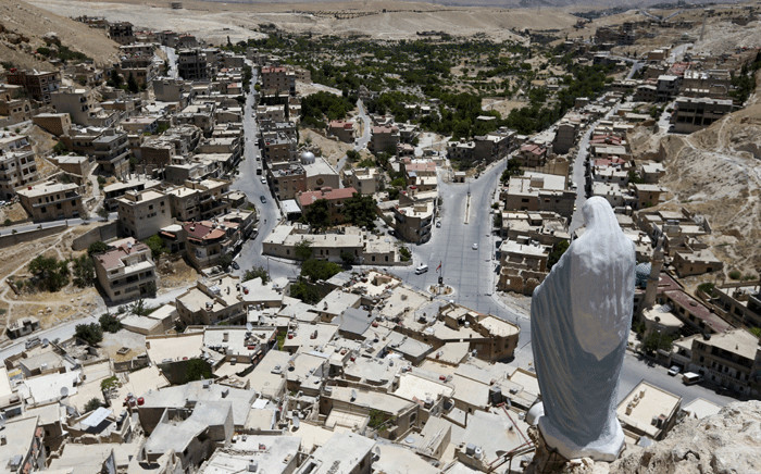 A statue of the Virgin Mary overlooks the village of Maalula, north of the Syrian capital Damascus, on June 29, 2021. One of the world's oldest Christian settlements where residents still speak the language of Jesus, Maalula once drew in thousands of visitors a year to visit its churches and monasteries, as well as to hear its inhabitants speak Aramaic. Picture: Louai Beshara / AFP