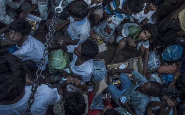 Myanmarese Muslim Rohingya residents sit inside a police truck in Birem Bayuen in Indonesias East Aceh province on 20 May 2015. Hundreds of starving boatpeople were rescued off Indonesia as Myanmar for the first time offered to help ease a regional migrant crisis blamed in part on its treatment of the ethnic Rohingya minority. Picture: AFP.