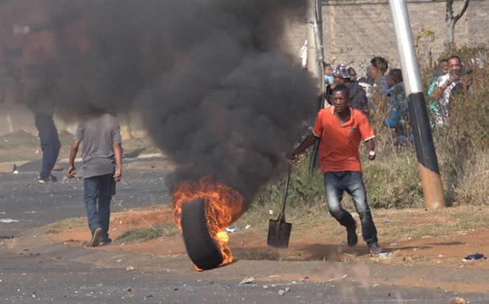 A protester in Ennerdale pushes a burning tyre into the road. Picture: Louise McAuliffe/EWN.