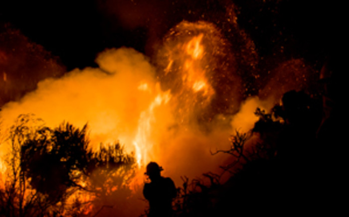 FILE: A firefighter battles a blaze on Boyes Drive in Muizenberg during fires that ravaged the Cape Peninsula in March 2015. Picture: Thomas Holder/EWN